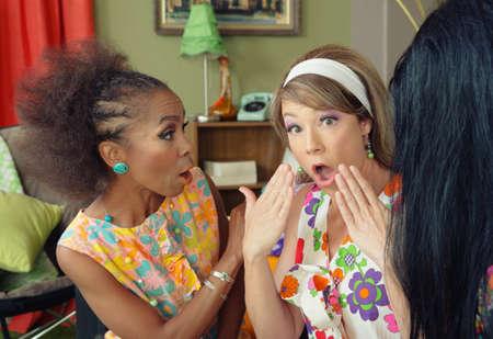 Trio of concerned ladies in 1960s dress talking