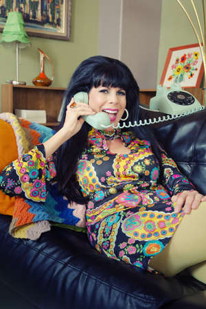 Happy smiling woman in paisley on rotary telephone