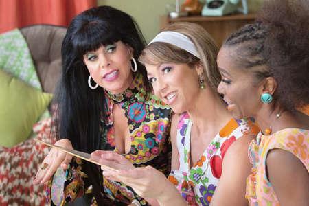 Drie verschillende glimlachende vrouwelijke vrienden op zoek naar vintage LP Stockfoto