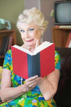 Uneasy single senior woman in green reading a book Stock Photo