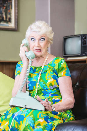 Cringing pretty senior woman in green on telephone