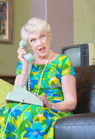 obscenity: Angry European senior female on phone in 1960s fashion