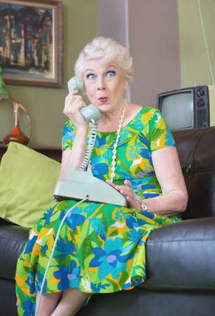 chismes: Intrigado sola femenino senior en tel�fono rotatorio Foto de archivo