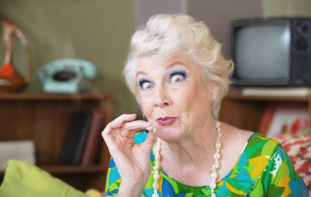 Excited Caucasian senior woman in green smoking marijuana Stockfoto