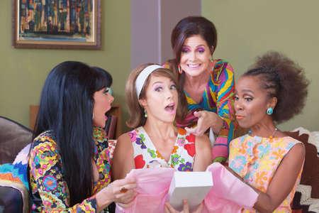 Leuke verrast vrouw houdt doos met vrienden op feestje Stockfoto