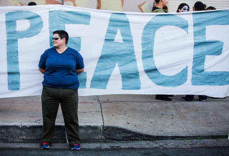 TUCSON, AZUSA - NOVEMBER 09: Unidentified woman in front of peace banner at the All Souls Procession on November 09, 2014 in Tucson, AZ, USA. Editöryel