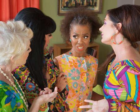 avergonzado: Grupo diverso de damas 1960 de estilo discutiendo Foto de archivo