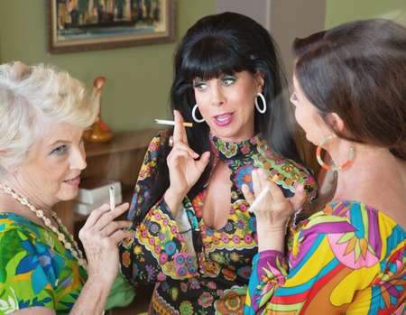 Group of three 1960s style women gossiping and smoking Stockfoto