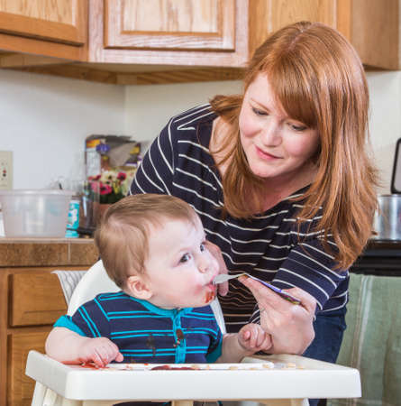 messy house: A woman feeds her baby juice in the kitchen Stock Photo