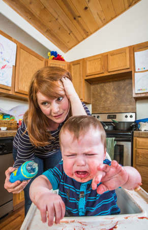 chaos: Grumpy baby in kitchen is being fed from bottle