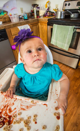 Curious baby in kitchen is looking upwards
