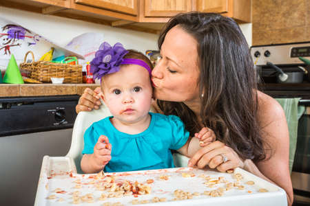 messy kitchen: Woman in a messy kitchen kisses her baby