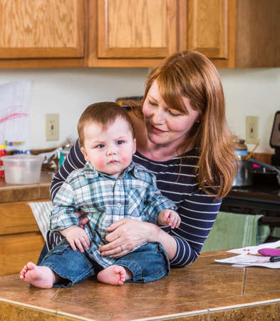 A woman in the kitchen poses with her baby