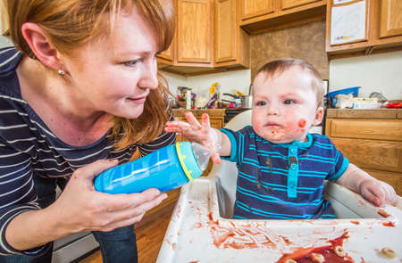 messy house: A woman in the kitchen feeds her baby from bottle