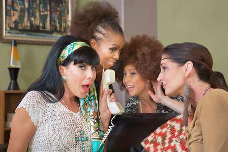 suspenso: Cuatro mujeres de mediana edad lindos escuchar por tel�fono Foto de archivo