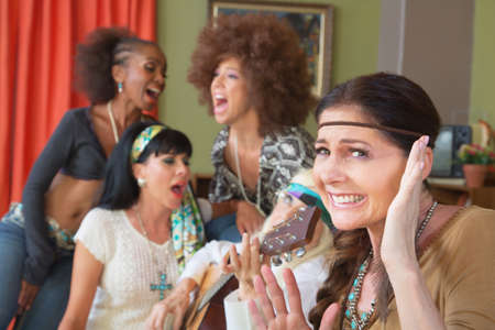 bothered: Lady cringing as group of friends sing and play music Stock Photo
