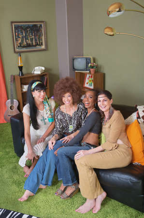 Group of four hippies sitting on leather sofa 스톡 콘텐츠