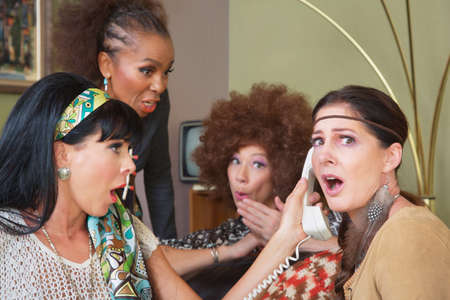 Embarrassed group of female friends listening to telephone photo