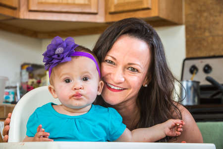 messy kitchen: Mother in messy kitchen smiles as baby eats