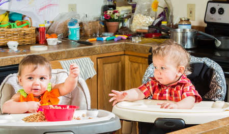 messy: Two babies eating breakfast together in highchairs