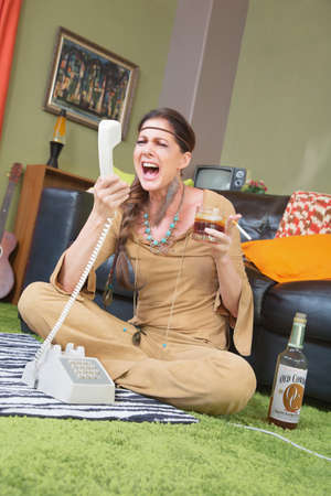 insulted: Drunk 1960s woman with cigarette yelling at telephone