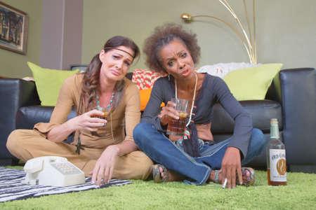 miserable: Pair of miserable 1960s women holding drinks