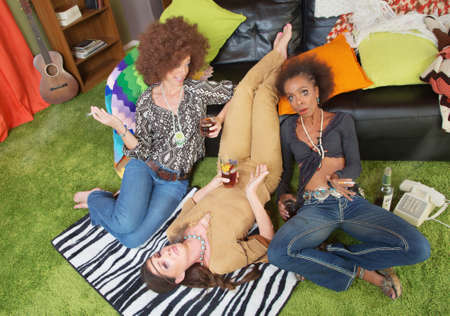 substance abuse: Three drunk women in 1960s clothing gossiping
