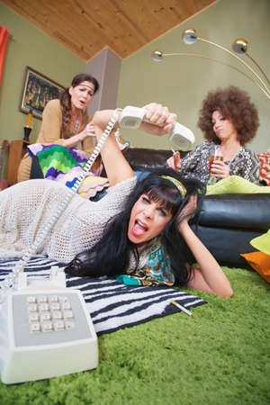 obnoxious: Angry woman laying on rug hanging up phone