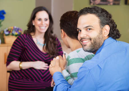 surrogate: Smiling Latino man with wife and surrogate mother