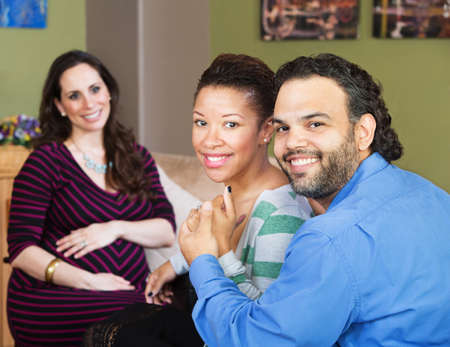 Smiling Hispanic couple sitting with beautiful surrogate mother Foto de archivo