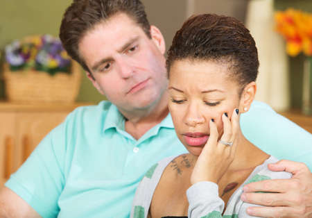 the spouse: Anxious beautiful young spouse with concerned husband