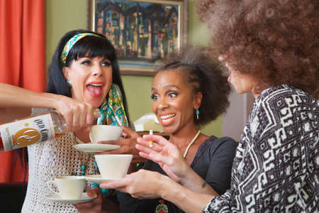 indulging: Mixed group of three excited women drinking booze in teacups Stock Photo
