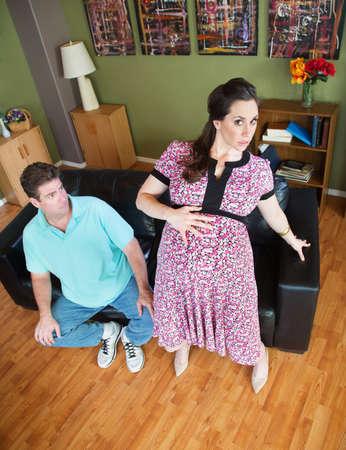 levantandose: Marido viendo torpe esposa embarazada levantarse de sof� Foto de archivo