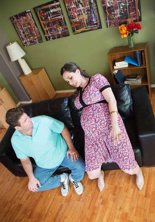 clumsy: El hombre mira a la mujer embarazada torpe en el sof� Foto de archivo