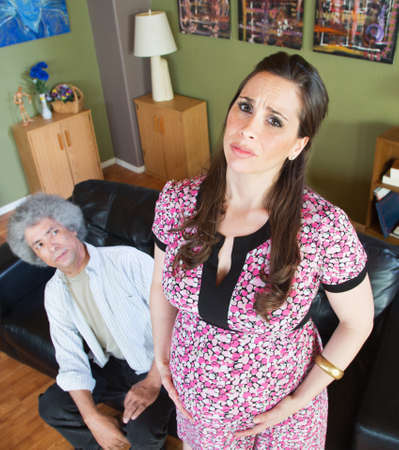 miserable: Husband looking at miserable pregnant wife holding belly