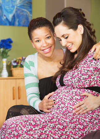 Smiling African woman touching her partner's pregnant belly