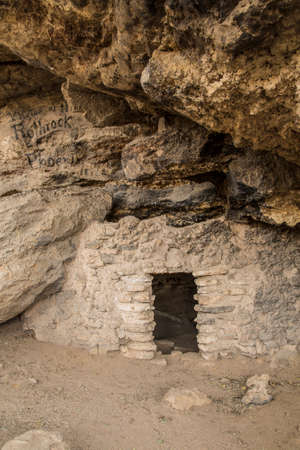 the dwelling: Cliff dwelling with historic paint graffiti advertisement