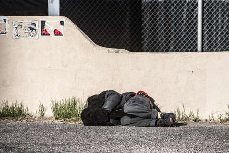 1 person: Homeless person sleeping near wall in parking lot Stock Photo