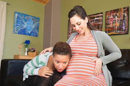 Lesbian spouse of pregnant woman listening to her womb photo