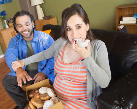 craving: Greedy pregnant woman with hungry partner on sofa