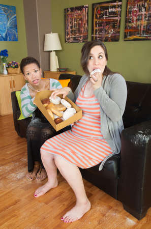 snacking: Barefoot pregnant woman with surprised partner eating donuts Stock Photo