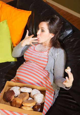 Pregnant woman with box of donuts licking her fingers