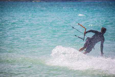 Male kite surfer moving over ocean surface photo