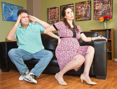 insensitive: Frustrated husband next to pregnant wife with backache