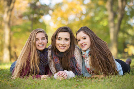 Three happy Caucasian teen girls sitting together Stock Photo