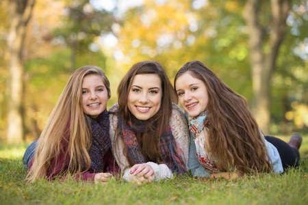 Tres muchachas adolescentes de raza caucásica felices sentados juntos