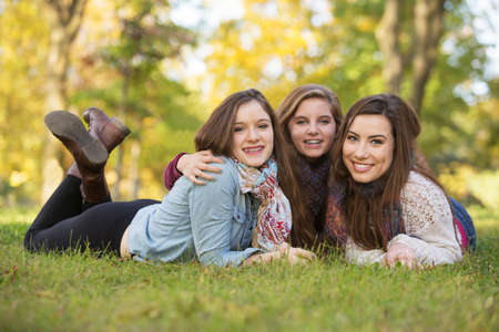 Trio of happy teen girls laying down on grass