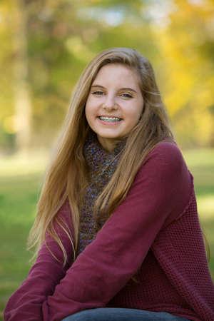 cute braces: Beautiful teenage girl in red sweater sitting outdoors