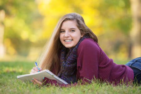 cute braces: Female teen with braces taking notes while laying on ground Stock Photo