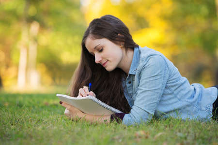 Grinning young woman writing on notebook outdoors